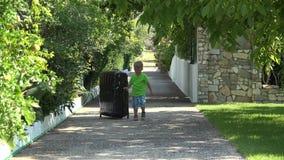 Rapaz pequeno que puxa uma mala de viagem enorme na aleia, saindo feliz filme