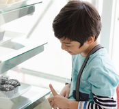 Rapaz pequeno que seleciona o bolo na loja da padaria Fotos de Stock
