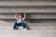 Rapaz pequeno que senta no staors Foto de Stock