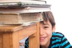Rapaz pequeno que senta-se atrás da cadeira de madeira com completamente dos livros, educação imagens de stock