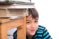 Rapaz pequeno que senta-se atrás da cadeira de madeira com completamente dos livros, educação imagem de stock royalty free