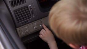 Rapaz pequeno que senta-se atrás da roda de um carro, pressiona o botão para abrir o tronco filme