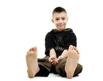 Rapaz pequeno que senta-se com os pés descalços, imagem de stock