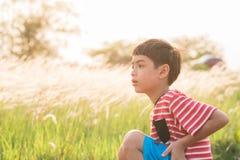 Rapaz pequeno que senta-se com tempo dourado do por do sol do campo de gramas Imagens de Stock