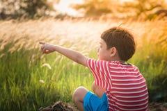 Rapaz pequeno que senta-se com tempo dourado do por do sol do campo de gramas Fotografia de Stock Royalty Free