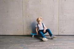 Rapaz pequeno que senta-se em um skate Fotos de Stock Royalty Free