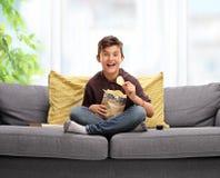 Rapaz pequeno que senta-se em um sofá e que come microplaquetas de batata Fotografia de Stock Royalty Free