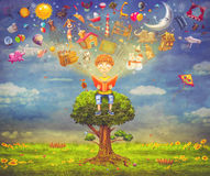 Rapaz pequeno que senta-se na árvore e que lê um livro Imagens de Stock