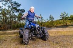 Rapaz pequeno que senta-se na bicicleta do quadrilátero Fotografia de Stock