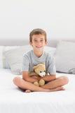 Rapaz pequeno que senta-se na cama que guardara seu urso de peluche Imagens de Stock Royalty Free