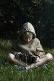 Rapaz pequeno que senta-se na grama e que usa o tablet pc Foto de Stock Royalty Free