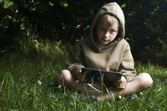 Rapaz pequeno que senta-se na grama e que usa o tablet pc Foto de Stock