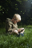 Rapaz pequeno que senta-se na grama e que usa o tablet pc Fotografia de Stock Royalty Free