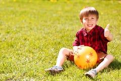 Rapaz pequeno que senta-se na grama que dá os polegares-acima Imagens de Stock Royalty Free