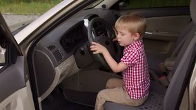 Rapaz pequeno que senta-se no assento do ` s do motorista atrás da roda, joga e gerencie a roda filme