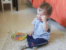 Rapaz pequeno que senta-se no assoalho, no ele virada do ` s e no grito O chil imagem de stock