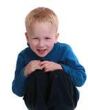 Rapaz pequeno que senta-se no fundo branco Imagens de Stock