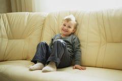 Rapaz pequeno que senta-se no sofá fotografia de stock royalty free