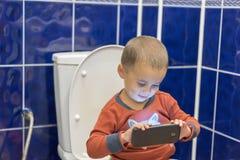 Rapaz pequeno que senta-se no toalete no banheiro em casa com utilização de um smartphone Menino da criança que senta-se no toale foto de stock royalty free