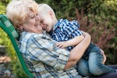 Rapaz pequeno que senta-se nos braços de sua avó amado Beijos e abraços delicados Gerações de amor imagem de stock royalty free