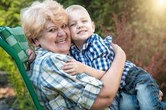 Rapaz pequeno que senta-se nos braços de sua avó amado Beijos e abraços delicados Gerações de amor foto de stock