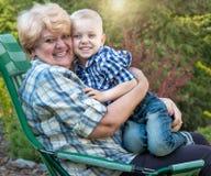 Rapaz pequeno que senta-se nos braços de sua avó amado Beijos e abraços delicados Gerações de amor imagens de stock