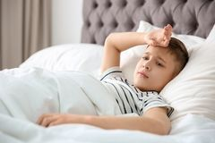 Rapaz pequeno que sofre da dor de cabeça ao encontrar-se na cama fotos de stock
