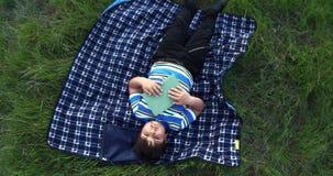 Rapaz pequeno que sonha após o livro de leitura é mentiras no tapete na grama video estoque