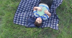 Rapaz pequeno que sonha após o livro de leitura é mentiras no tapete na grama filme