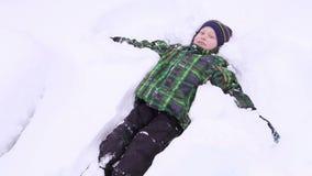 Rapaz pequeno que sorri e que faz o anjo da neve video estoque