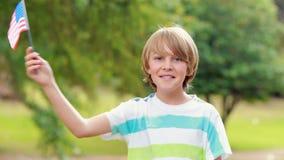 Rapaz pequeno que sorri na câmera e na bandeira americana de ondulação vídeos de arquivo