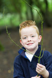 Rapaz pequeno que sorri nas madeiras Fotografia de Stock