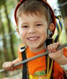 Rapaz pequeno que sorri no parque da aventura fotografia de stock