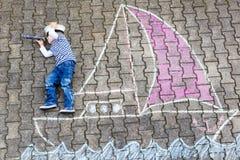 Rapaz pequeno que tem o divertimento com o desenho da imagem do navio com giz Fotos de Stock Royalty Free