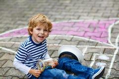 Rapaz pequeno que tem o divertimento com o desenho da imagem do navio com giz Imagens de Stock