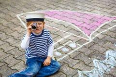 Rapaz pequeno que tem o divertimento com o desenho da imagem do navio com giz Imagens de Stock Royalty Free
