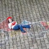 Rapaz pequeno que tem o divertimento com o desenho do carro de corridas com gizes Fotografia de Stock