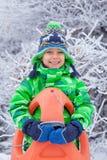 Rapaz pequeno que tem o divertimento com o trenó no parque do inverno Imagem de Stock