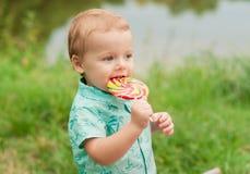 Rapaz pequeno que tem o divertimento e que come o pirulito grande exterior foto de stock royalty free