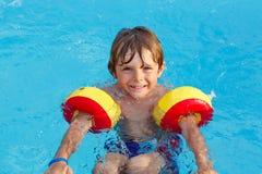 Rapaz pequeno que tem o divertimento em uma piscina Fotografia de Stock Royalty Free