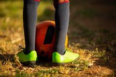 Rapaz pequeno que tem o divertimento que joga um jogo de futebol do futebol no dia de verão Do Active esporte do jogo fora para c Imagens de Stock
