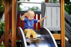 Rapaz pequeno que tem o divertimento na corrediça exterior de playground/on imagens de stock royalty free