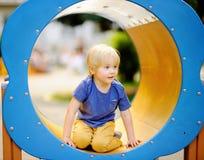 Rapaz pequeno que tem o divertimento na corrediça exterior de playground/on foto de stock