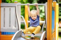 Rapaz pequeno que tem o divertimento na corrediça exterior de playground/on fotos de stock royalty free