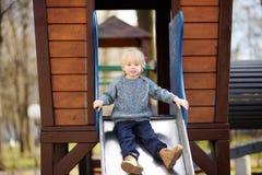 Rapaz pequeno que tem o divertimento na corrediça exterior de playground/on foto de stock royalty free