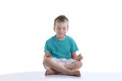 Rapaz pequeno que tenta concentrar-se para a meditação fotos de stock royalty free