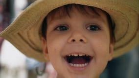 Rapaz pequeno que tenta em um chapéu em uma loja e em um sorriso Compra dos miúdos vídeos de arquivo