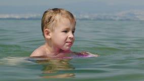 Rapaz pequeno que tenta nadar a bordo no mar vídeos de arquivo