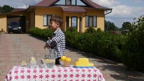 Rapaz pequeno que tenta vender a limonada vídeos de arquivo