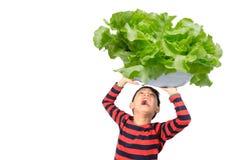 Rapaz pequeno que toma a bacia grande enorme de vegetal sobre sua cabeça no fundo branco fotos de stock